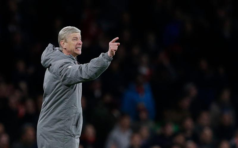 Arsenal manager Arsene Wenger gestures to his players during the English Premier League soccer match between Arsenal and Leicester City at the Emirates Stadium