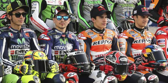 (L-R) Yamaha MotoGP riders Valentino Rossi of Italy and Jorge Lorenzo of Spain and Honda MotoGP riders Marc Marquez of Spain and compatriot Dani Pedrosa pose for a group photo before the start of the free practice session of the MotoGP World Championship at the Losail International circuit in Doha March 20, 2014. REUTERS/Fadi Al-Assaad (QATAR - Tags: SPORT MOTORSPORT)