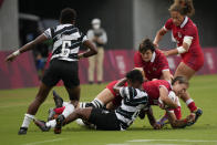 Canada's Kaili Lukan, carrying the ball, is tackled by Fiji's Viniana Riwai, as Canada's Britt Benn tries to assist, in their women's rugby sevens match at the 2020 Summer Olympics, Thursday, July 29, 2021 in Tokyo, Japan. (AP Photo/Shuji Kajiyama)