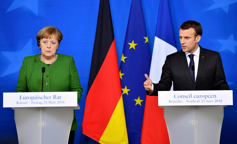 FILE - In this March 23, 2018, file photo, French President Emmanuel Macron, right, and German Chancellor Angela Merkel speak at a news conference in Brussels. The future of the landmark Iran nuclear deal hangs in the balance and its survival may depend on the unlikely success of last-minute European interventions with President Donald Trump. Macron and Merkel are to visit Washington separately later in April and will likely be the last foreign leaders invested in the deal to see Trump ahead of his mid-May deadline for the accord to be strengthened. (AP Photo/Geert Vanden Wijngaert, File)