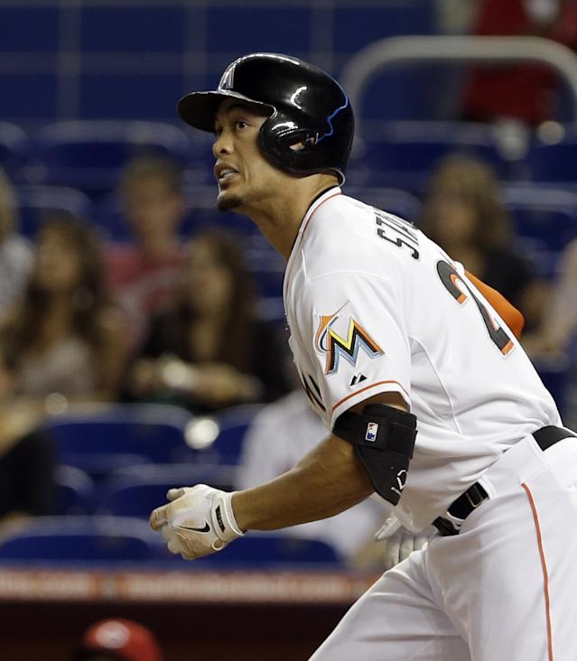Miami Marlins' Giancarlo Stanton watches as the ball clears the left field fence after hitting a solo home run against the Cincinnati Reds in the first inning of a baseball game in Miami, Thursday, July 31, 2014. (AP Photo/Alan Diaz)