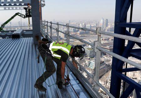A worker installs an edge trim on the AXA IM - Real Assets Twentytwo building in London, Britain April 20, 2018. Picture taken April 20, 2018.  REUTERS/Darren Staples