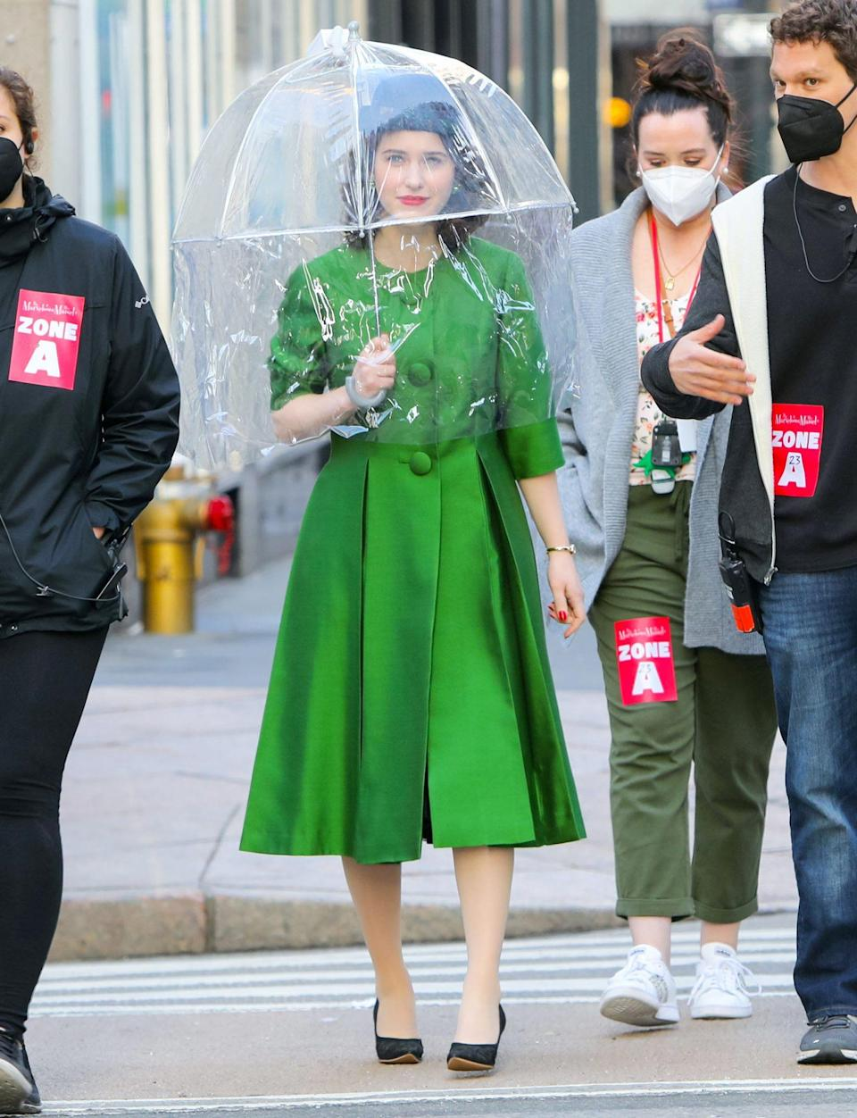 <p>Rachel Brosnahan wears a vibrant green satin dress and a bold red lip on the set of <em>The Marvelous Mrs. Maisel</em> on Tuesday in N.Y.C.</p>