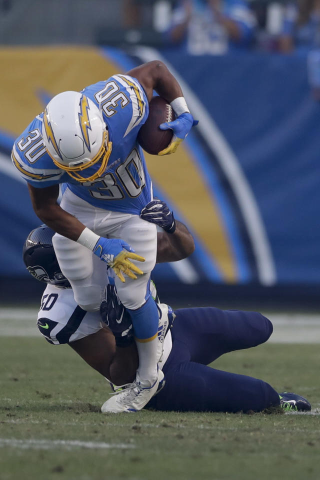 Los Angeles Chargers running back Austin Ekeler is tackled by Seattle Seahawks outside linebacker K.J. Wright during the first half of an NFL preseason football game Saturday, Aug. 24, 2019, in Carson, Calif. (AP Photo/Gregory Bull)