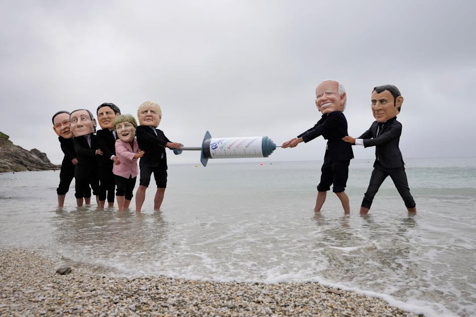 Activists wearing giant heads of the G7 leaders tussle over a giant COVID-19 vaccine syringe at Swanpool Beach in Falmouth, Cornwall, England, June 11, 2021. Depicted from left to right, Japan's Prime Minister Yoshihide Suga, Italy's Prime Minister Mario Draghi, Canadian Prime Minister Justin Trudeau, German Chancellor Angela Merkel, British Prime Minister Boris Johnson, U.S. President Joe Biden and French President Emmanuel Macron.