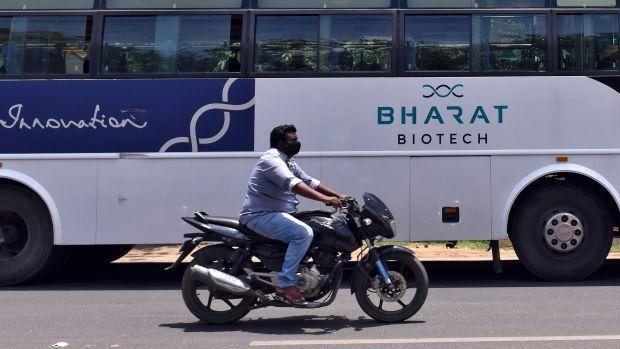 A man rides his motorbike past a parked bus of India's biotechnology company Bharat Biotech outside its office in Hyderabad