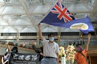 FILE PHOTO: A pro-democracy demonstrator waves the British colonial Hong Kong flag during a protest against new national security legislation in Hong Kong