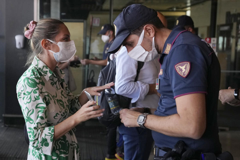 FILE - In this Sept. 1, 2021, file photo, a police officer checks a passenger's phone at Porta Garibaldi train station, in Milan, Italy. In both the U.S. and the EU, officials are struggling with the same question: how to boost vaccination rates to the max and end a pandemic that has repeatedly thwarted efforts to control it. Italy is the first major European economy to require the COVID pass to access places of work across all sectors. (AP Photo/Luca Bruno, File)
