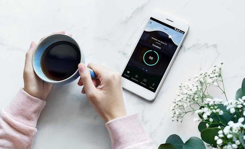 Woman checks the air quality in her home using the DARWIN System's accompanying mobile app.