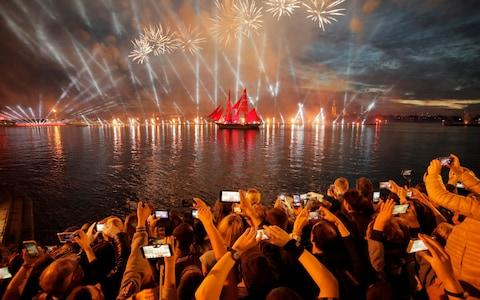 People watch fireworks and a brig with scarlet sails on the Neva River during the Scarlet Sails festivities marking school graduation in St Petersburg - Credit: Photo/Dmitri Lovetsky