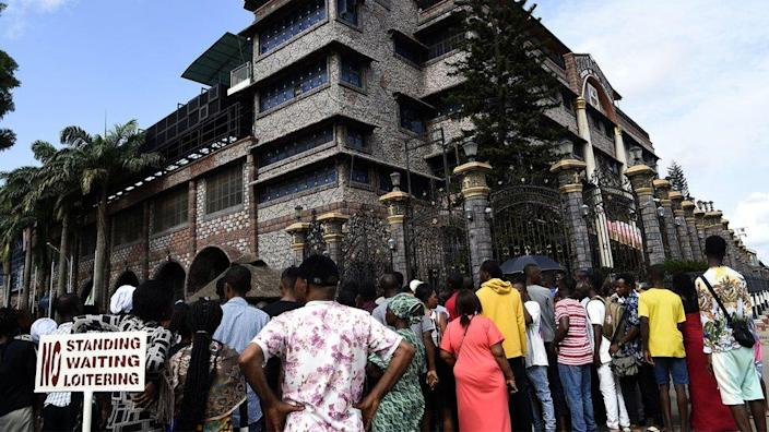 Residents and church members gather at the main gate of The Synagogue Church of All Nations (SCOA) headquarters to mourn the death of late Nigerian pastor TB Joshua, in the Ikotun distrcit of Lagos on June 6, 2021