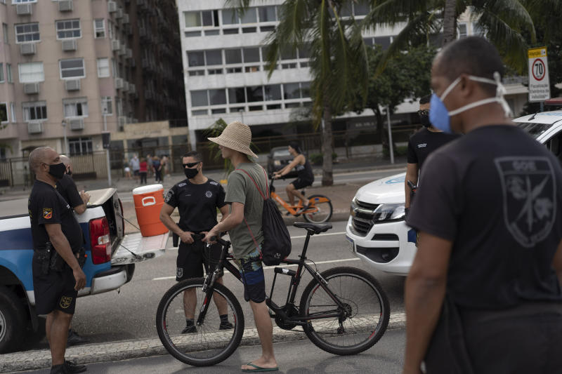 Municipal guards stop a man on a bike to tell him to wear a mask at Copacabana beach amid the outbreak of the new coronavirus in Rio de Janeiro, Brazil, Sunday, July 12, 2020. (AP Photo/Leo Correa)
