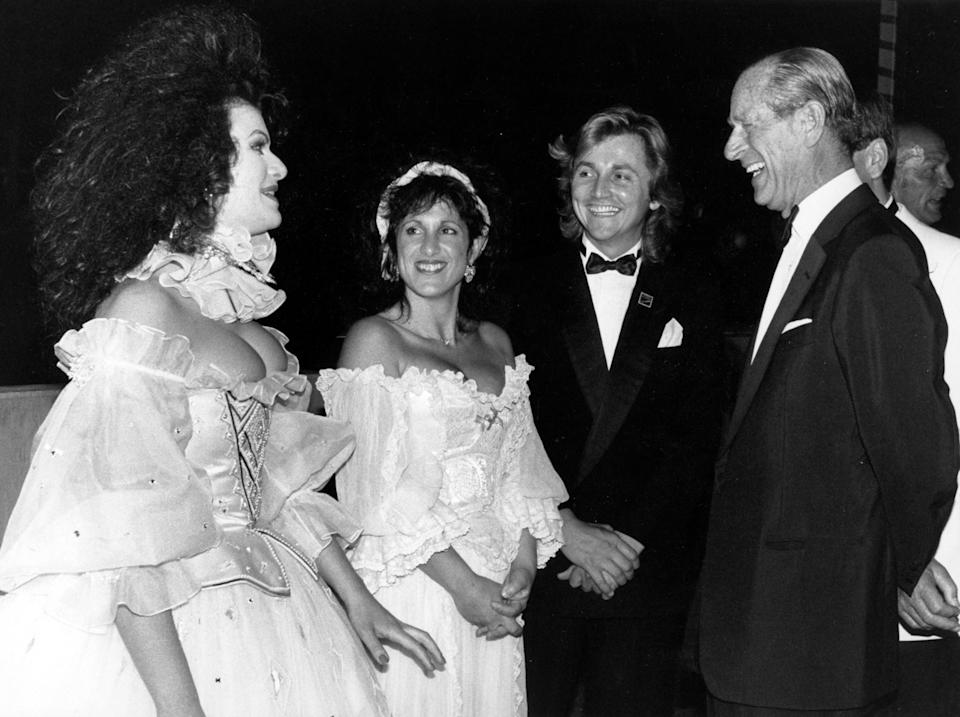 <p>An amused Duke of Edinburgh, patron of Elizabethan-themed Berkeley Square Ball, London, with actress Cleo Rocos (left) and dress designers Elizabeth and David Emmanuel, who made the wedding dress for the Princess of Wales. They donated a dress for auction and boxer Henry Cooper (far right) acted as one of the auctioneers. </p>