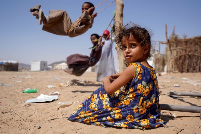Girl sits as other children play on swings at a camp for internally displaced people in Marib, Yemen