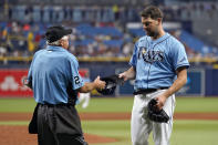 Home plate umpire Tom Hallion (20) checks Tampa Bay Rays starting pitcher Rich Hill's hat for any foreign substances as he leaves the game against the Boston Red Sox during the fifth inning of a baseball game Wednesday, June 23, 2021, in St. Petersburg, Fla. (AP Photo/Chris O'Meara)