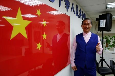 """Chang An-lo, known as """"White wolf"""", leader of the Chinese Unification Promotion Party (CUPP), poses next to a China national flag after an interview in Taipei"""