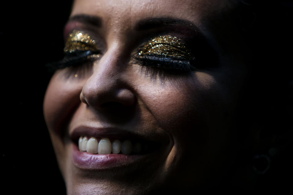 """A member of the """"Desliga da Justica"""" street band gets dressed in her costume in Rio de Janeiro, Brazil, Sunday, Feb. 14, 2021. The group's performance was broadcast live on social media for those who were unable to participate in the carnival due to COVID restrictions after the city's government officially suspended Carnival and banned street parades or clandestine parties. (AP Photo/Bruna Prado)"""