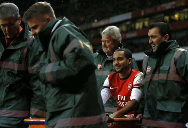Arsenal's Theo Walcott, is carried from the pitch on a stretcher after an injury during the English FA Cup third round soccer match between Arsenal and Tottenham Hotspur at the Emirates Stadium in London, Saturday, Jan. 4, 2014. (AP Photo/Kirsty Wigglesworth)