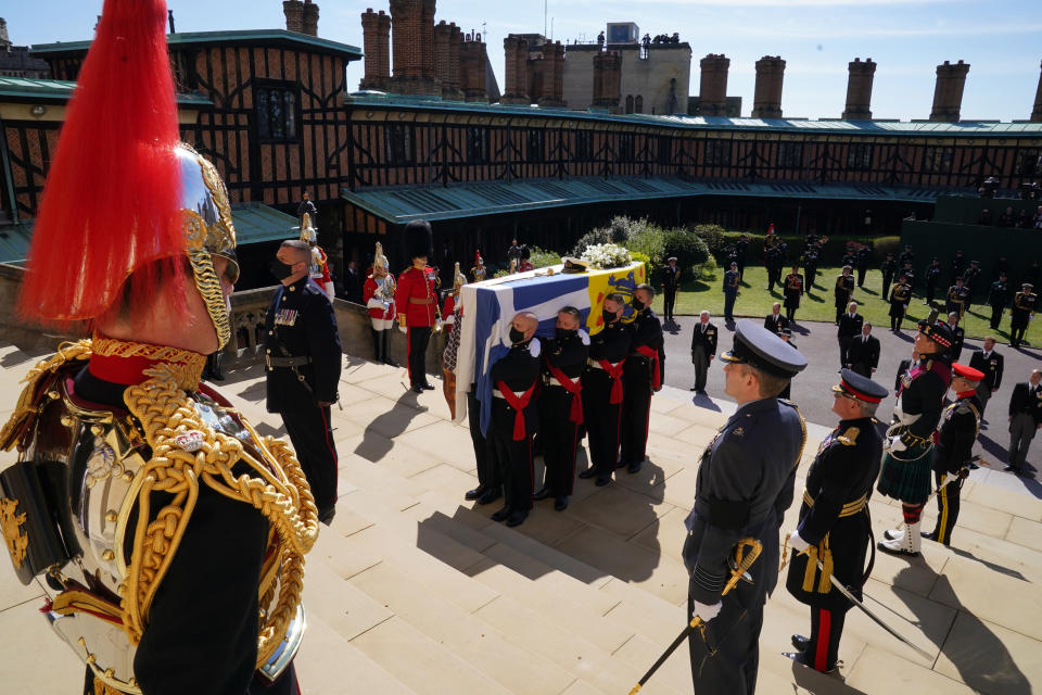 The coffin is held on the steps of St George's Chapel during the procession of Britain Prince Philip's funeral at Windsor Castle, Windsor, England, Saturday April 17, 2021. Prince Philip died April 9 at the age of 99 after 73 years of marriage to Britain's Queen Elizabeth II. (Arthur Edwards/Pool via AP)