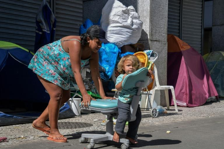 Daniela Rosa Neves and her son, Riquelme, play in Patriarca Square in the center of Sao Paulo, Brazil, where they live on the street, on August 19, 2021 (AFP/NELSON ALMEIDA)