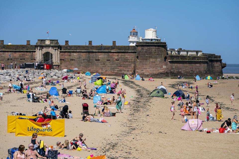 Sunbathers enjoy the weather in New Brighton, Wirral, on what could be the hottest day of the year (Peter Byrne/PA) (PA Wire)