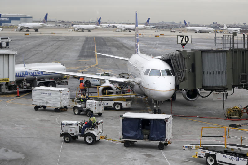 In this Jan. 23, 2019, photo a United Airlines jet is parked at a gate as luggage handlers pull carts near the terminal at Newark Liberty International Airport in Newark, N.J. United Airlines reports financial results on Tuesday, July 16. (AP Photo/Julio Cortez)