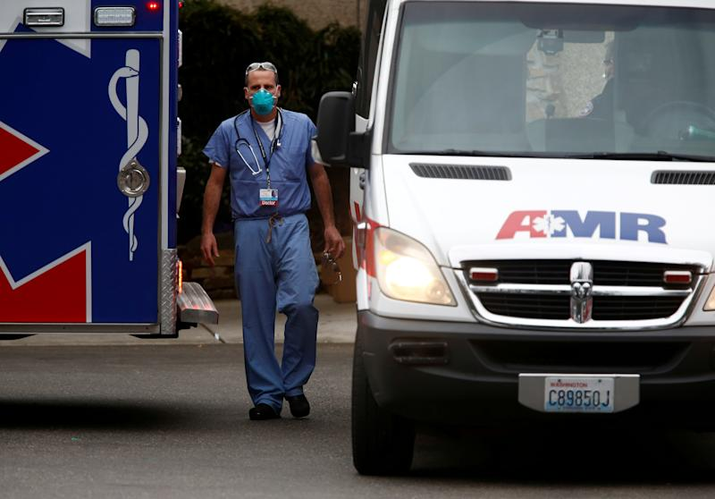 (In this file photo, a doctor walks near an ambulance at the Life Care Center of Kirkland, a long-term care facility linked to several confirmed coronavirus cases, in Kirkland, Washington, U.S. March 5, 2020. (Lindsey Wasson/Reuters/File Photo)