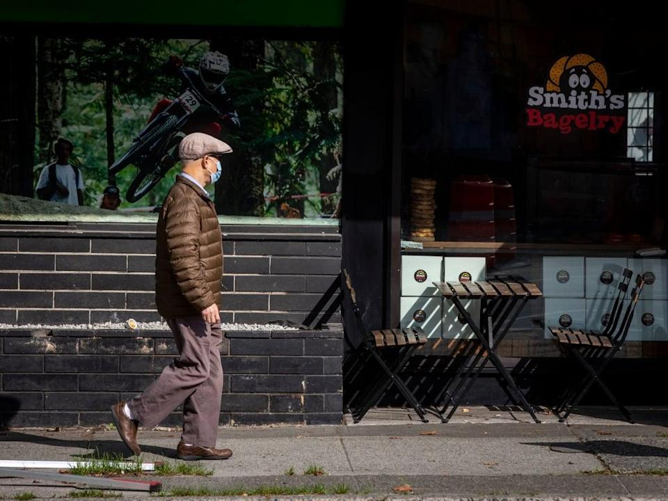 A man wearing a mask walks by a restaurant patio in Vancouver, British Columbia on Monday, Oct. 4, 2021.  (Ben Nelms/CBC - image credit)