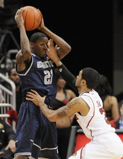 Louisville's Peyton Siva, right, gets his hand in the face of Georgetown's Jason Clark during the second half of an NCAA college basketball game Wednesday, Dec. 28, 2011, in Louisville, Ky. Georgetown defeated Louisville 71-68. (AP Photo/Timothy D. Easley)