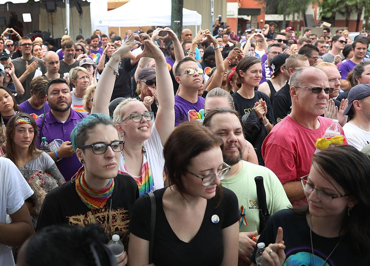 <p>People mourning the loss of family, friends and loved ones in the mass shooting at the Pulse gay nightclub gather together outside the club during a one-year anniversary memorial service on June 12, 2017 in Orlando, Florida. (Joe Raedle/Getty Images) </p>