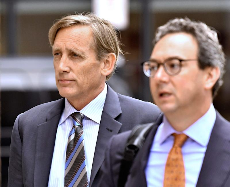 Jeffrey Bizzack, left, arrives at federal court with a member of his defense team, Wednesday July 24, 2019, in Boston where he is expected to plead guilty to charges for allegedly paying to get his son into the University of Southern California as a fake volleyball recruit. (AP Photo/Josh Reynolds) ORG XMIT: MACR103
