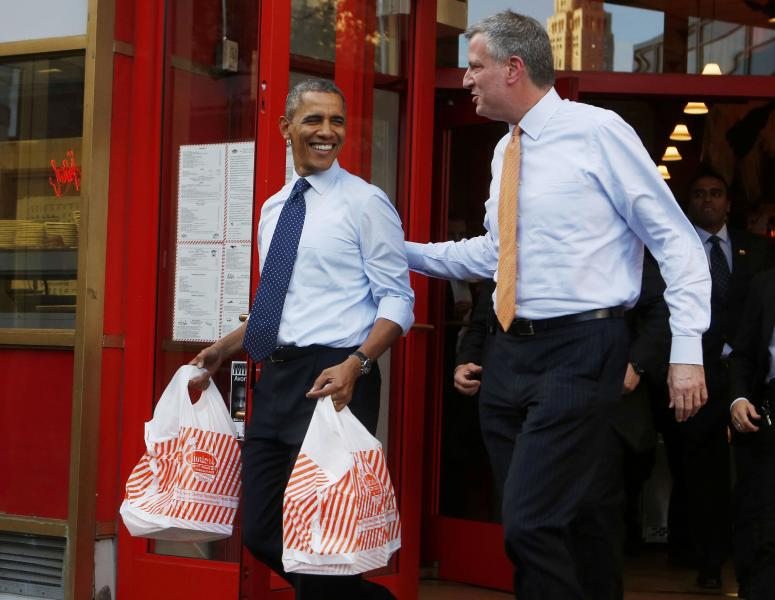U.S. President Barack Obama walks out with two bags of cheesecake from Junior's Restaurant next to Democratic Mayoral candidate Bill de Blasio in Brooklyn, October 25, 2013. REUTERS/Larry Downing (UNITED STATES - Tags: POLITICS FOOD)