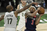 Washington Wizards' Bradley Beal (3) is fouled by Milwaukee Bucks' P.J. Tucker (17) during the first half of an NBA basketball game Wednesday, May 5, 2021, in Milwaukee. (AP Photo/Aaron Gash)