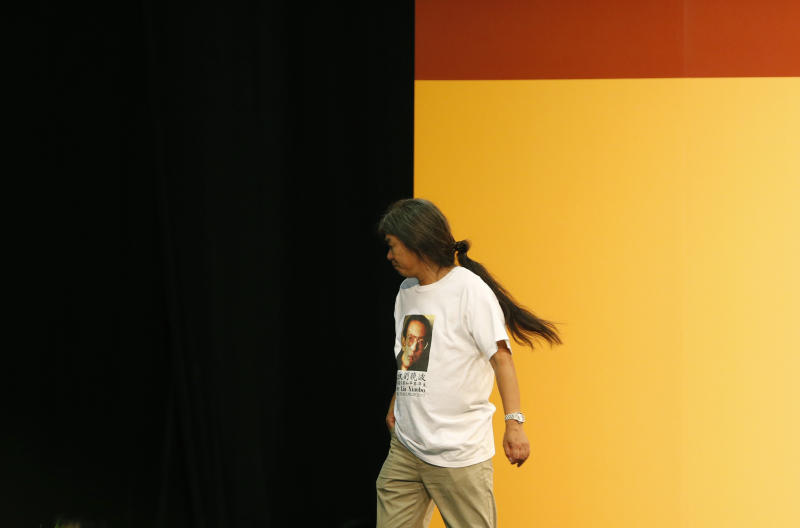 """Leung Kwok-hung, also known as """"Long Hair,"""" of the pro-democracy League of Social Democrats leaves after winning a seat on the Legislative Council in Hong Kong, Monday, Sept. 10, 2012. Hong Kong voters cast ballots in legislative elections Sunday that will help determine the eventual shape of full democracy that Beijing has promised the former British colony. (AP Photo/Kin Cheung)"""