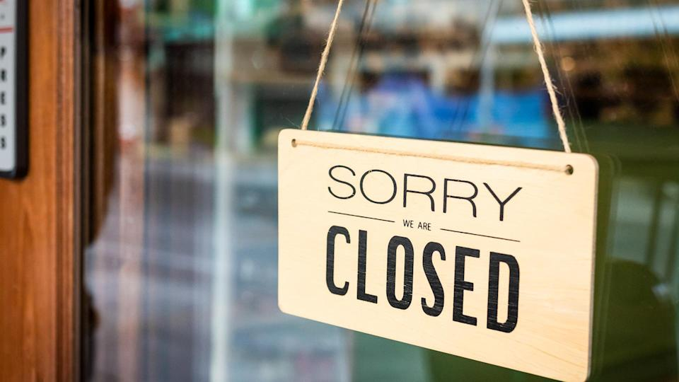 Sorry we are closed sign board hanging on a door of cafe.