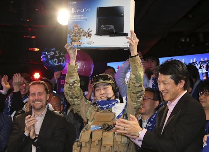 Sony Computer Entertainment Inc. President and CEO Andrew House, left, Sony Computer Entertainment Japan President Hiroshi Kawano, right, and first customer of PlayStation 4 , center, pose for photo during launch event in Tokyo, Saturday, Feb. 22, 2014. (AP Photo/Koji Sasahara)