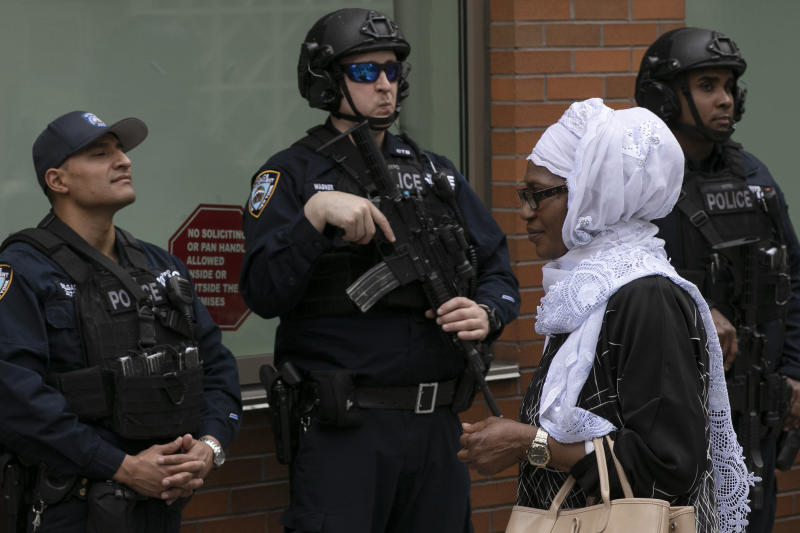 A woman leaves the Islamic Cultural Center of New York under increased police security following the shooting in New Zealand on March 15, 2019.