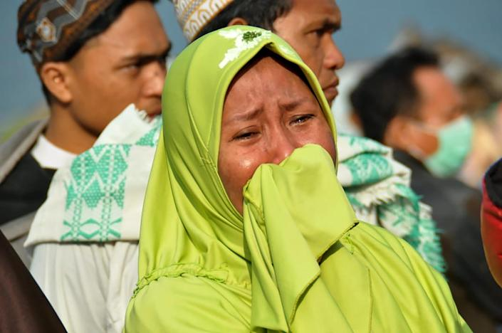 <p>A woman cries as people look at the damages after an earthquake and a tsunami hit Palu, on Sulawesi island on Sept. 29, 2018. (Photo: Muhammad Rifki/AFP/Getty Images) </p>