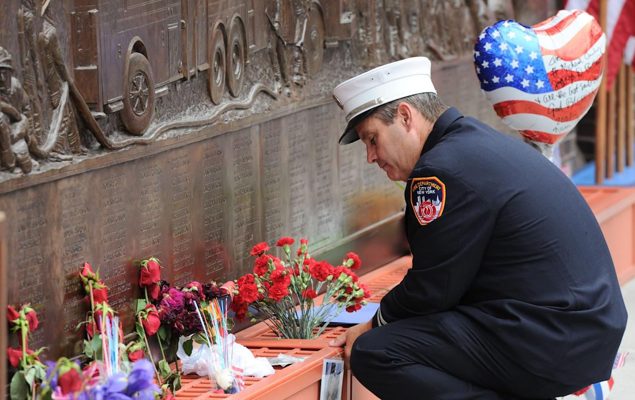 A New York city firefighter pauses at the firefighters memorial wall that displays the names of victims of Sept. 11 at ground zero on the 10th anniversary of the terrorist attacks in New York, Sunday, September 11, 2011. (AP Photo/The Canadian Press, Sean Kilpatrick)