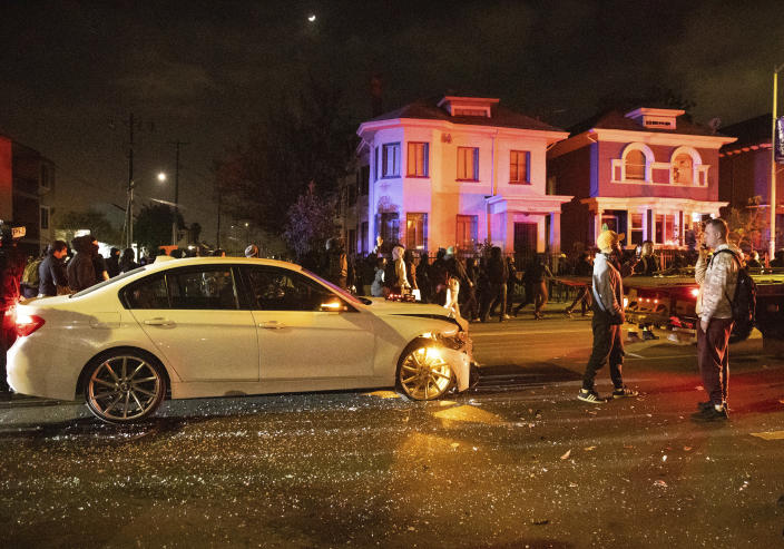 Several hundred demonstrators walk past the scene of a car crash during a protest against police brutality in Oakland, Calif., on Friday, April 16, 2021. (AP Photo/Ethan Swope)
