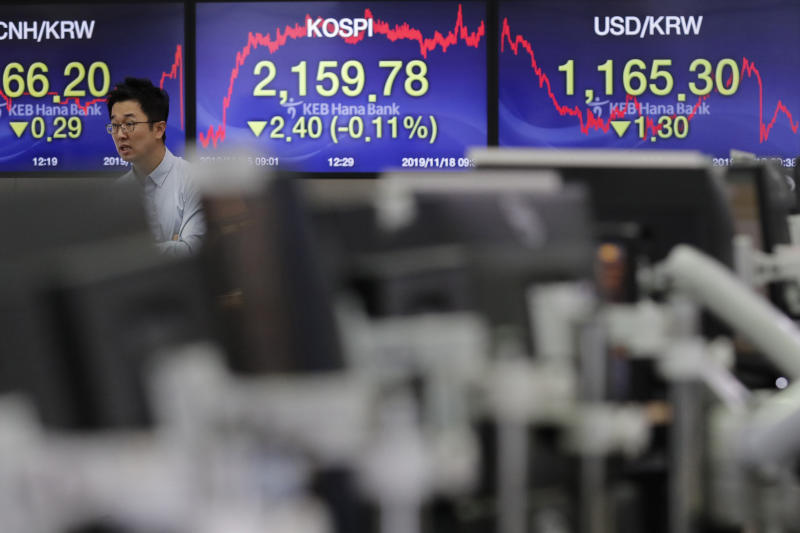 A currency trader walks near screens showing the Korea Composite Stock Price Index (KOSPI), center, and the foreign exchange rate between U.S. dollar and South Korean won, right, at the foreign exchange dealing room in Seoul, South Korea, Monday, Nov. 18, 2019. Asian shares are mixed Monday in a cautious mode after Wall Street closed out the week with milestones as the Dow Jones Industrial Average crossed 28,000 for the first time and the S&P 500 and Nasdaq hit record highs. (AP Photo/Lee Jin-man)