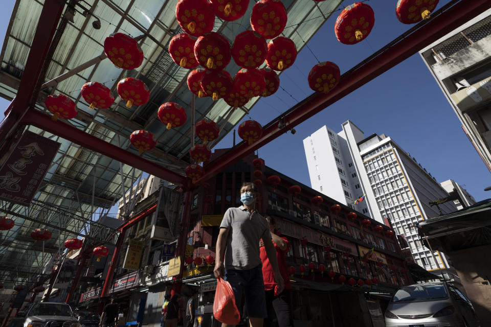 A Chinese couple wear face mask walks with Chinese lunar new year decoration at China town in Kuala Lumpur, Malaysia, Sunday, Feb. 7, 2021. The movement control order (MCO) currently enforced across the country, has been extended to Feb. 18, effectively covering the Chinese New Year festival that falls on Feb. 12 this year. (AP Photo/Vincent Thian)