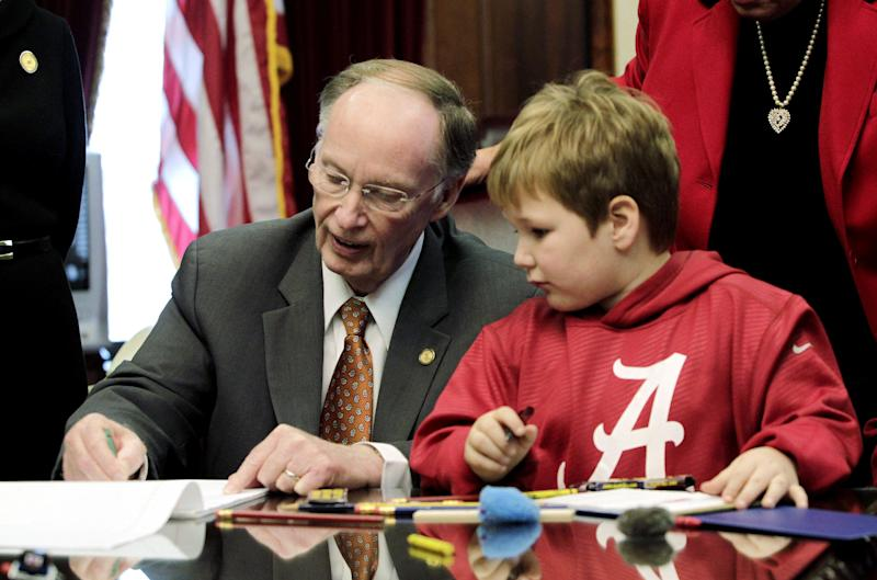 In this photo provided by the Governor's office, Gov. Robert Bentley, left, draws with 6-year-old Ethan Gilman during a visit to the Governor's Office in Montgomery, Ala. on Wednesday, Feb. 13, 2012. Ethan was held hostage in an underground bunker in a near week-long standoff in Midland City, Ala. (AP Photo/Alabama Governor's Office, Jamie Martin)
