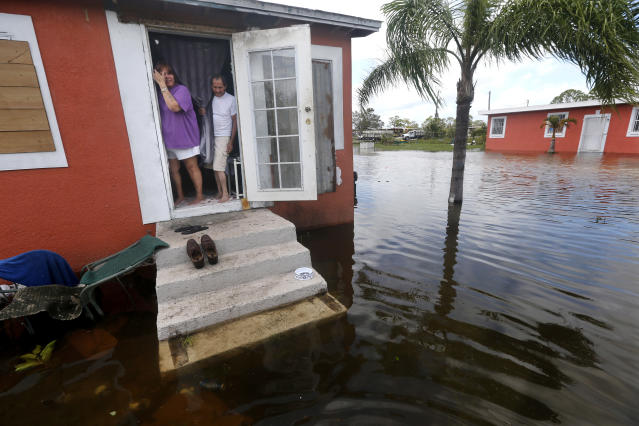 <p>Quintana and Liz Perez look out at the flooding outside their home in the aftermath of Hurricane Irma in Immokalee, Fla., Sept. 11, 2017. (Photo: Gerald Herbert/AP) </p>