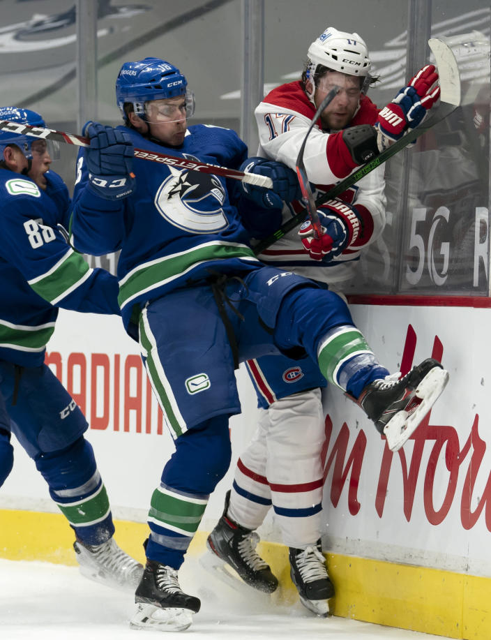 Vancouver Canucks right wing Jake Virtanen (18) goes into the boards with Montreal Canadiens right wing Josh Anderson (17) during the first period of an NHL hockey game Wednesday, Jan. 20, 2021, in Vancouver, British Columbia. (Jonathan Hayward/The Canadian Press via AP)
