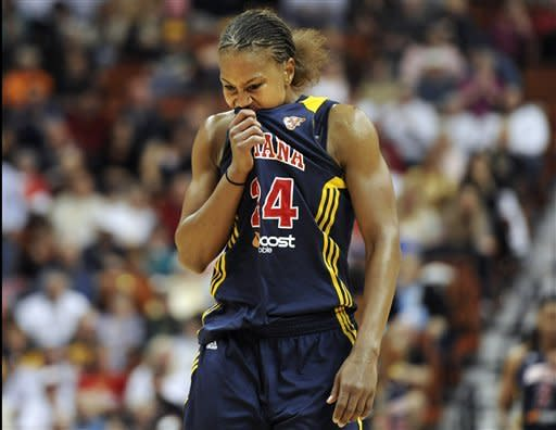 Indiana Fever's Tamika Catchings wipes her face with her shirt during the first half of Game 3 of the WNBA basketball Eastern Conference finals against the Connecticut Sun in Uncasville, Conn., Thursday, Oct. 11, 2012. (AP Photo/Jessica Hill)