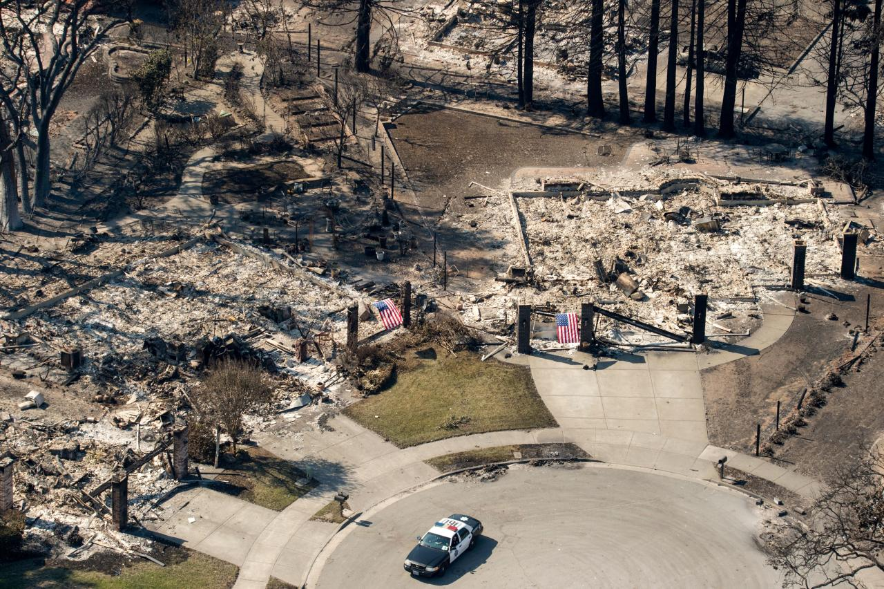 <p>In this aerial view, a police officer drives near burned properties in Santa Rosa, Calif., on Oct. 12, 2017. (Photo: Josh Edelson/AFP/Getty Images) </p>