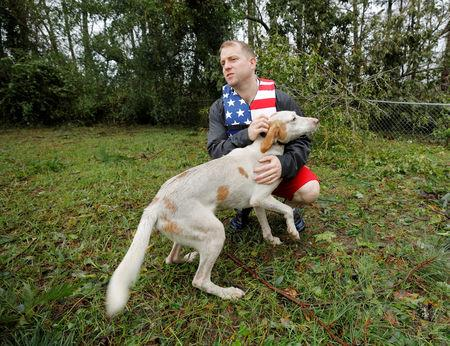 Volunteer rescuer Ryan Nichols of Longview, Texas, pets one of the dogs that were left caged by an owner who fled rising floodwater in the aftermath of Hurricane Florence in Leland, North Carolina, U.S., September 16, 2018. REUTERS/Jonathan Drake