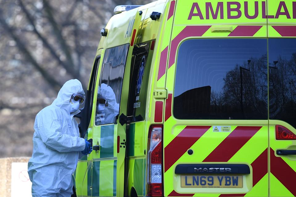 A member of the ambulance service wearing personal protective equipment is seen leading a patient (unseen) into an ambulance at St Thomas' Hospital in London on March 24, 2020. - Britain's leaders on Tuesday urged people to respect an unprecedented countrywide lockdown, saying that following advice to stay at home would stop people dying of coronavirus. (Photo by DANIEL LEAL-OLIVAS / AFP) (Photo by DANIEL LEAL-OLIVAS/AFP via Getty Images)