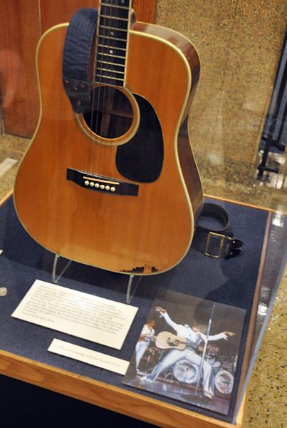 This April 22, 2013 photo shows a Martin D-35 guitar played by Elvis Presley during the final tour before his death in 1977 at the National Music Museum in Vermillion, S.D. The instrument was donated to the museum by Robert Johnson, a guitarist who played in the 1970s with Isaac Hayes and John Entwistle's Ox. Presley smashed the guitar after a string and the shoulder strap broke during a February 1977 show in St. Petersburg, Fla., and it was given that night to a woman in the audience. (AP Photo/Dirk Lammers)